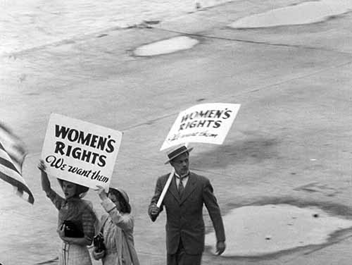 The ladies' man Billings evasively joins a suffragist parade.