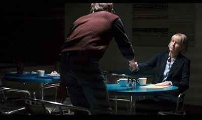 """Director Katherine Hudson (uncredited*), CEO of multinational Brady Corp., gets her news at a tiny plastic table in a cafeteria with dirty dishes."""""""