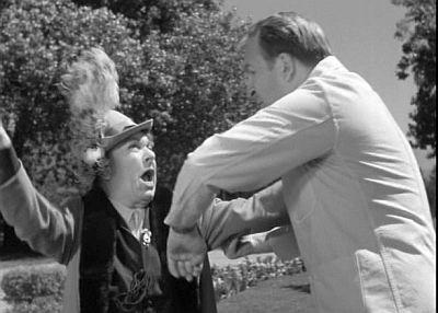 Veta (Josephine Hull) resists asylum attendant Wilson (Jesse White).