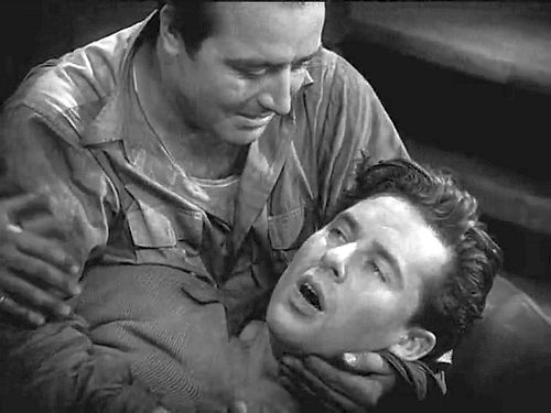 "A fun-house mirror: Top, Wings' Jack (Charles Rogers) cradles a dying David (Richard Arlen) after having shot down his plane; the scene as played is sentimental ""hokum."" Below, Hell's Angels Roy (James Hall) cradles dying brother Monte (Ben Lyon) after having shot him in the back to prevent him from divulging information to their German captors; the scene as played is naturalistic realism. Jack will be forgiven by David's mother; Roy will die in front of a firing squad."