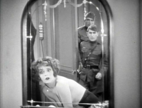 "Risqué (but innocent) ""hokum"": Top, in Wings, Mary (Clara Bow) embraces Jack (Charles Rogers) in a Paris hotel room while attempting to sober him up to report to his unit for the ""big push."" Moments later (below), as she is changing from a dancer's dress to her Women's Motor Transport Corps uniform, MPs break in and, suspecting the worst, have her sent back to the US for violating the Army's morals code (for women)."
