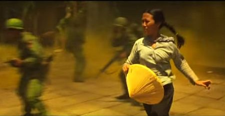 Screenshot from Apocalypse Now: a female VC races to throw a grenade in the helicopter