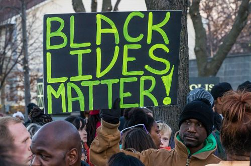 "An activist holds a ""Black Lives Matter"" signs outside the Minneapolis Police Fourth Precinct building following the officer-involved shooting of Jamar Clark on November 15, 2015. Photo: Tony Webster tony@tonywebster. Used by permission of the photographer; licensed through Wikimedia Commons."