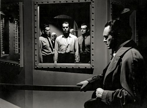 Fred MacMurray, flanked by guards, and Edward G. Robinson: Double Indemnity