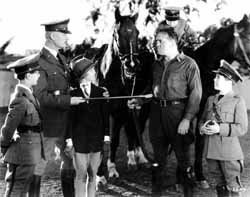 Figure 3: Chips off the old block in Square Shoulders. From left to right, Eddie (Philippe DeLacy), the camp commandmant (Clarance Geldhart), the boys' love interest (Anita Louise), 'Slag' Collins (Louis Wolheim), and the square-shouldered Tad (Frank Coghlan, Jr.)