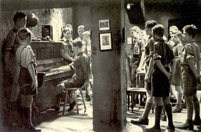 Figure 6: Guarded entertainment: The Hitler Youth at ease, while still at attention, in their party scene from Hitlerjunge Quex. The piece being played is, of course, their theme.